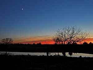 Crescent moon and susnet over a farm pond